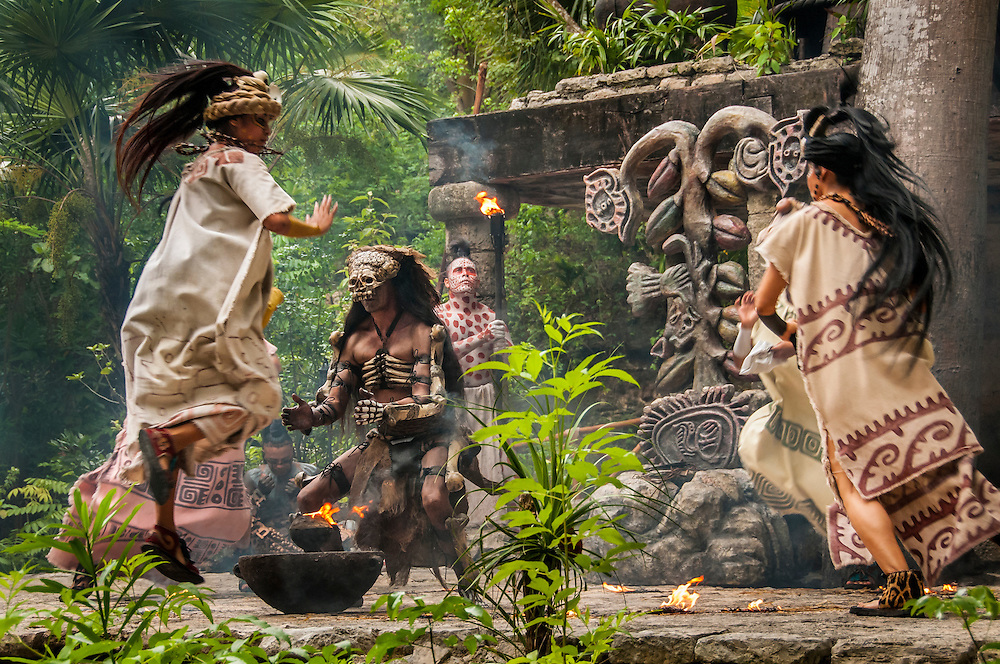 """Women dancers and man portraying Ah puch, Lord of the Underworld (or God of Death), during the Maya culture performance """"Los Rostros de Ek chuah"""", honoring the Mayan God of Cacao, at Xcaret park, Riviera Maya, Mexico."""