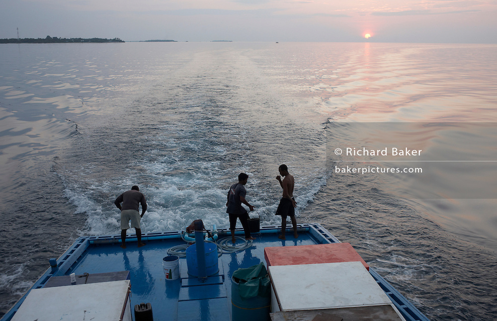 The crew aboard a traditional dhoni fishing boat prepare for another day's fishing for tuna on the Indian Ocean, Maldives.