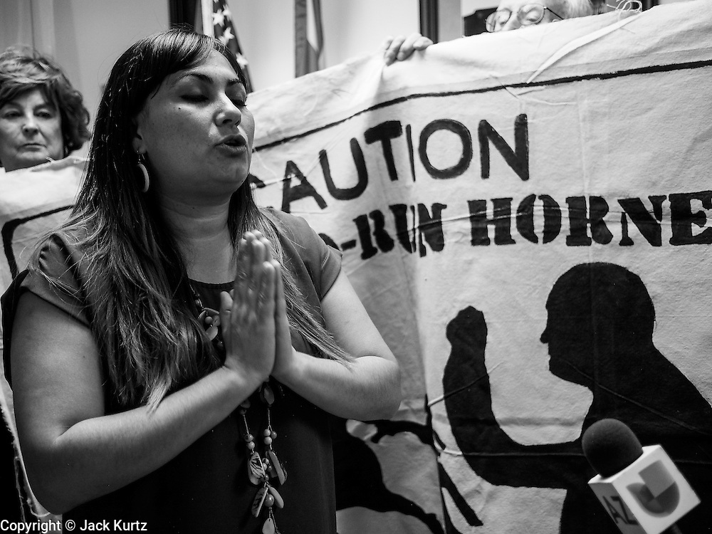 17 OCTOBER 2013 - PHOENIX, AZ: A woman prays while talking about the DREAM Act in the offices of Arizona Attorney General Tom Horne. About 100 people came to the office of Arizona Attorney General Tom Horne to protest the decision by Horne to sue community colleges in Maricopa County that charge DREAM Act students who are residents of Arizona out of state tuition rather than in state resident tuition. Nearly 10 people were arrested in a planned civil disobedience during the protest.     PHOTO BY JACK KURTZ