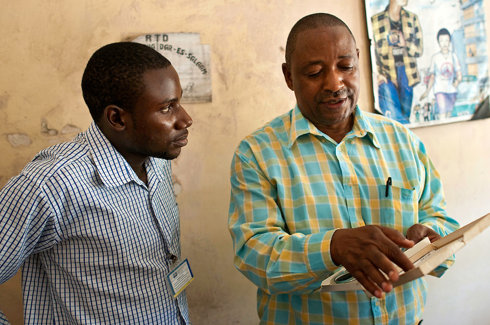 Bruno shows Benson Rukantabula, a young Tanzanian who also helped found the Tanzania Heritage Project, how the inlays and designs on the reel labeling are a hallmark of who archived the recording. Benson hopes that the country can preserve its heritage and inspire young Tanzanian artists through the music of the past, by digitizing the archives.