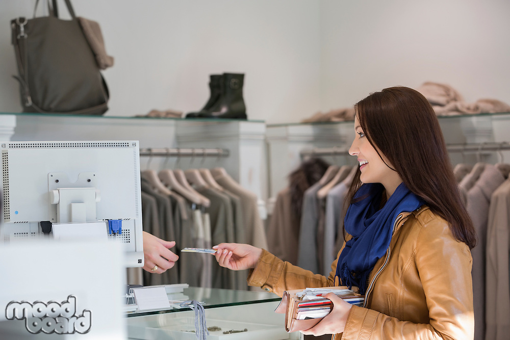 Young woman giving credit card to cashier