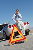 Warning triangle in front of man on cell phone by sports car