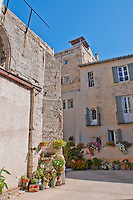Courtyard of stone houses with flowers in Arles, France.