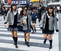 Japanese schoolgirls crossing Hatchiko crossing in Shibuya Tokyo Japan