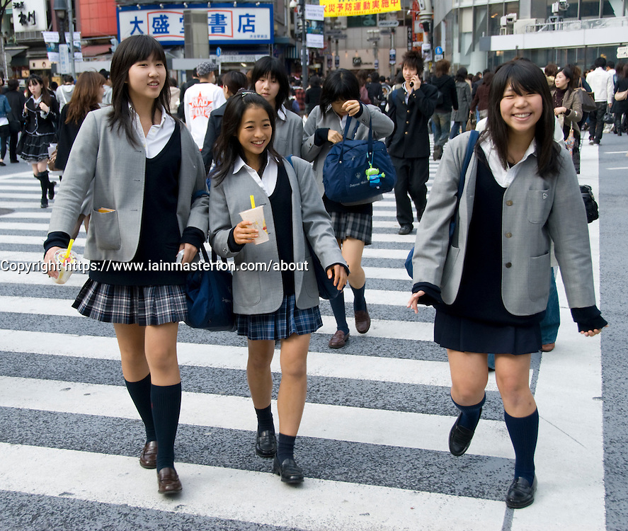 Japanese schoolgirls crossing Hatchiko crossing in Shibuya Tokyo Japan