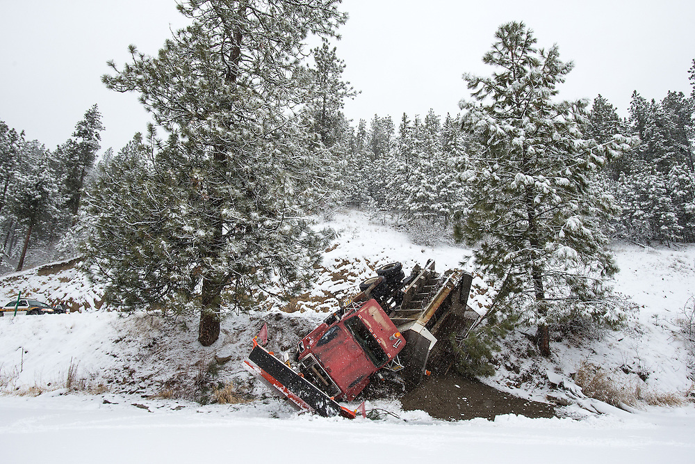 GABE GREEN/Press<br /> <br /> A Kootenai County Groomer Program truck slumps over the edge of East Fernan Lake Road Wednesday after the driver maneuvered to avoid colliding with an oncoming van. Icy conditions made recovery of the vehicle difficult for tow trucks, causing an extended delays for drivers along East Fernan Lake Road.