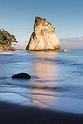 Initially formed by volcanic eruptions, the white ignimbrite that makes up Te Hoho Rock continues to be sculpted by the incoming tide.  Coromandel, New Zealand.