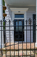 New Orleans, LA, USA -- May 26, 2019.  Vertical shot of the front porch of a house behind a gate in the Garden District  in New Orleans, LA.