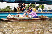 "17 NOVEMBER 2012 - BANGKOK, THAILAND:  A woman selling tourist curios alongside a tourist boat on the Chao Phraya River in Bangkok. Bangkok used to be known as the ""Venice of the East"" because of the number of waterways the criss crossed the city. Now most of the waterways have been filled in but boats and ships still play an important role in daily life in Bangkok. Thousands of people commute to work daily on the Chao Phraya Express Boats and fast boats that ply Khlong Saen Saeb or use boats to get around on the canals on the Thonburi side of the river. Boats are used to haul commodities through the city to deep water ports for export.    PHOTO BY JACK KURTZ"