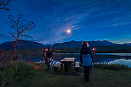 Two photographers and participants at my June 17 Night Photography Workshop in Waterton Lakes National Park, at Maskinonge, in the evening twilight, with the waxing crescent Moon (at centre) and noctilucent clouds (at right).  A single exposure with the Sigma 20mm lens and Nikon D750.