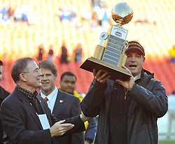 Nov 27, 2010; Kansas City, MO, USA; Brady Deeton, Chancellor at Missouri (left) and Kansas City Chiefs owner Clark Hunt (center) present the Lamar Hunt trophy to Missouri Tigers head coach Gary Pinkel after the Tigers defeated the Kansas Jayhawks 35-7 at Arrowhead Stadium. Mandatory Credit: Denny Medley-US PRESSWIRE