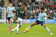 Freddie Ladapo (19) of Plymouth Argyle gets the ball past Michael Ihiekwe (4) of Accrington Stanley during the EFL Sky Bet League 1 match between Plymouth Argyle and Accrington Stanley at Home Park, Plymouth, England on 22 December 2018.