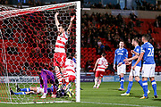 After Doncaster Rovers midfielder Tommy Rowe (10) header back across goal Doncaster Rovers defender Andrew Butler (6) celebrates as Portsmouth defender Christian Burgess (6) scores an own goal to make the score 2-0 during the EFL Sky Bet League 1 match between Doncaster Rovers and Portsmouth at the Keepmoat Stadium, Doncaster, England on 17 October 2017. Photo by Simon Davies.