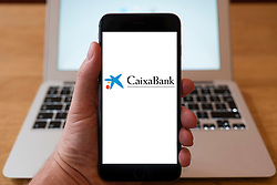 Using iPhone smartphone to display logo of CaixaBank the Spanish financial services company owned by the Catalan savings bank