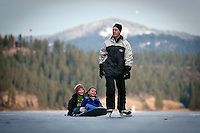JEROME A. POLLOS/Press..Anthony Hall tows his daughter Hannah, 5, and Wiley Pierce, also 5, on a sled while ice skating Friday on Fernan Lake.