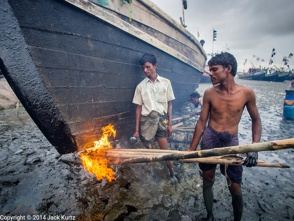 07 NOVEMBER 2014 - SITTWE, RAKHINE, MYANMAR: Workers apply tar, used as a water sealant, to a boat in the port of an IDP camp housing Rohingya Muslims near Sittwe. The boats were originally built as fishing boats but are increasingly being used by human traffickers to take people to Malaysia. The government of Myanmar has forced more than 140,000 Rohingya Muslims who used to live in Sittwe, Myanmar, into squalid Internal Displaced Person (IDP) camps. The forced relocation took place in 2012 after sectarian violence devastated Rohingya communities in Sittwe and left hundreds dead. None of the camps have electricity and some have been denied access to regular rations for nine months. Conditions for the Rohingya in the camps have fueled an exodus of Rohingya refugees to Malaysia and Thailand. Tens of thousands have put to sea in rickety boats hoping to land in Malaysia but sometimes landing in Thailand. The exodus has fueled the boat building boom on the waterfront near the camps. Authorities expect the pace of refugees fleeing Myanmar to accelerate during the cool season, December through February, when there are fewer storms in the Andaman Sea and Bay of Bengal.   PHOTO BY JACK KURTZ
