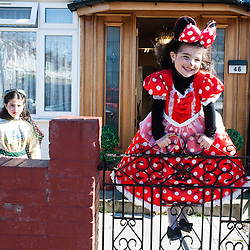 London, UK - 16 March 2014: Dassy, 10 (L) and Trany, 6 (R)  celebrate the festivity of Purim, dancing and singing in the streets at the sound of Yiddish music and visiting wealthy businessmen collecting for their charity