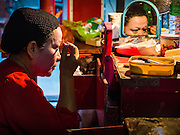 "30 JUNE 2016 - BANGKOK, THAILAND: A performer puts on her eye makeup before a Chinese opera performance at Chiao Eng Piao Shrine in Bangkok. Chinese opera was once very popular in Thailand, where it is called ""Ngiew."" It is usually performed in the Teochew language. Millions of Chinese emigrated to Thailand (then Siam) in the 18th and 19th centuries and brought their culture with them. Recently the popularity of ngiew has faded as people turn to performances of opera on DVD or movies. There are about 30 Chinese opera troupes left in Bangkok and its environs. They are especially busy during Chinese New Year and Chinese holidays when they travel from Chinese temple to Chinese temple performing on stages they put up in streets near the temple, sometimes sleeping on hammocks they sling under their stage.       PHOTO BY JACK KURTZ"