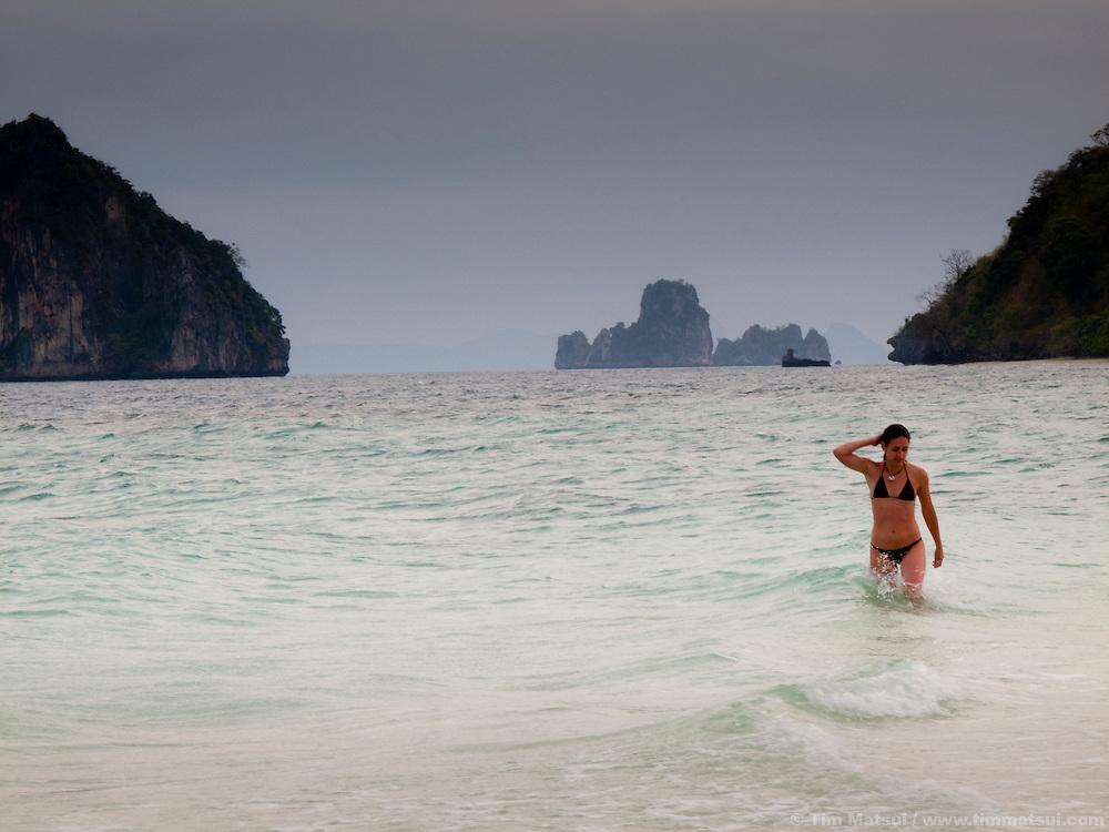 A woman wades through surf near Tonsai, Thailand.