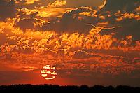 Boiling red clouds above setting sun create a stunning prairie sunset, near Qu'Appelle Valley Saskatchewan