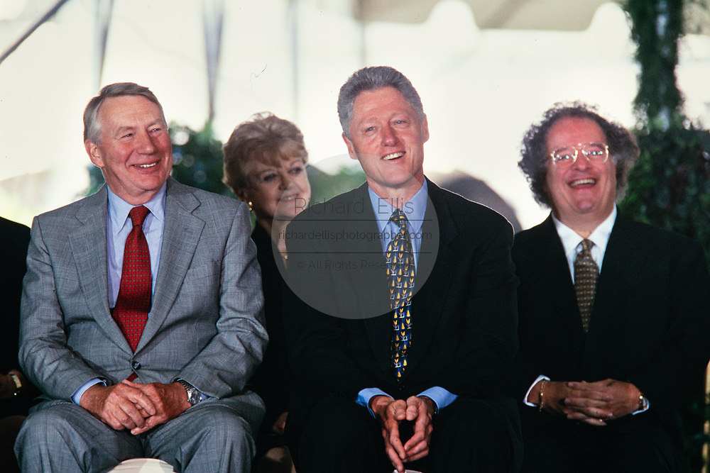 U.S. President Bill Clinton sits with Journalist Robert MacNeil, left, and Music Director of the Metropolitan Opera James Levine, right, during the National Medal of Arts and Humanities awards during a ceremony on the South Lawn of the White House September 29, 1997 in Washington, DC.