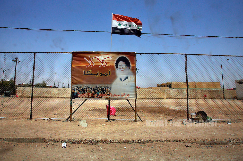 IRAQ, BASRA - JULY 4: A poster of the late Ayatollah Mohammed Bakr al Sadr, father of Mehdi Army leader Muqtada al Sadr, hangs on soccer-field fence below an Iraqi flag in the poverty stricken neighborhood of Hayaniyah, July 4, 2008 in Basra, Iraq. When British forces withdrew in 2007, Basra deteriorated into street battles between numerous Shiite militias and criminal gangs. In April 2008, Iraqi prime minister, Nouri al Maliki, sent two Iraqi army divisions to retake control of Basra. While the fighting has ended, unemployment is rife, at about 70 per cent. Since early 2008, Iraq's security situation has improved with oil production increasing, record government surplus and easing sectarian tensions. (Photo by Warrick Page)