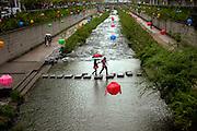 Der Cheonggyechon wurde in den 60er Jahren durch eine mehrspurige Strasse verdeckt. Inzwischen hat jedoch auch die Stadt Seoul den Wert von Gr¸nfl?chen erkannt und in einem aufwendigen Projekt die (ohnehin mit Sicherheitsm?ngeln behaftete) Strasse wieder entfernt. Entstanden ist ein neuer, nun allerdings k¸nstlicher Fluss quer durch das Zentrum der Stadt, dessen Wege zu einem Spaziergang einladen. F¸r die Feierlichkeiten von Buddhas Geburtstag (2. Mai diesen Jahres) wurde der Bereich mit bunten Lampions dekoriert...Cheonggyecheon is a nearly 6 km long, modern public recreation space in downtown Seoul, South Korea. The massive urban renewal project is on the site of a stream that flowed before the rapid post-war economic development required it to be covered by transportation infrastructure. The $900 million project attracted much criticism initially but opened in 2005 and is now popular among Seoul residents and tourists. For the celebration of Buddhas birthday (2nd of May this year) the area was decorated with colorful lampions.
