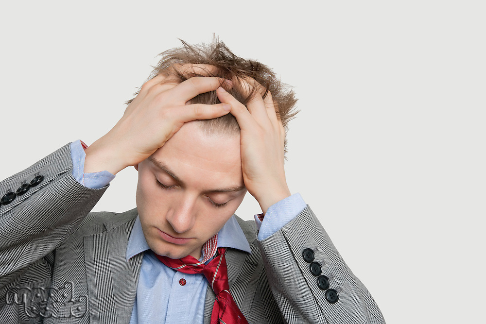 Close-up view of exhausted young businessman with hands in hair over colored background