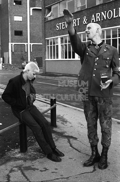 Skinhead doing a Nazis salute impersonation. UK, 1980s.