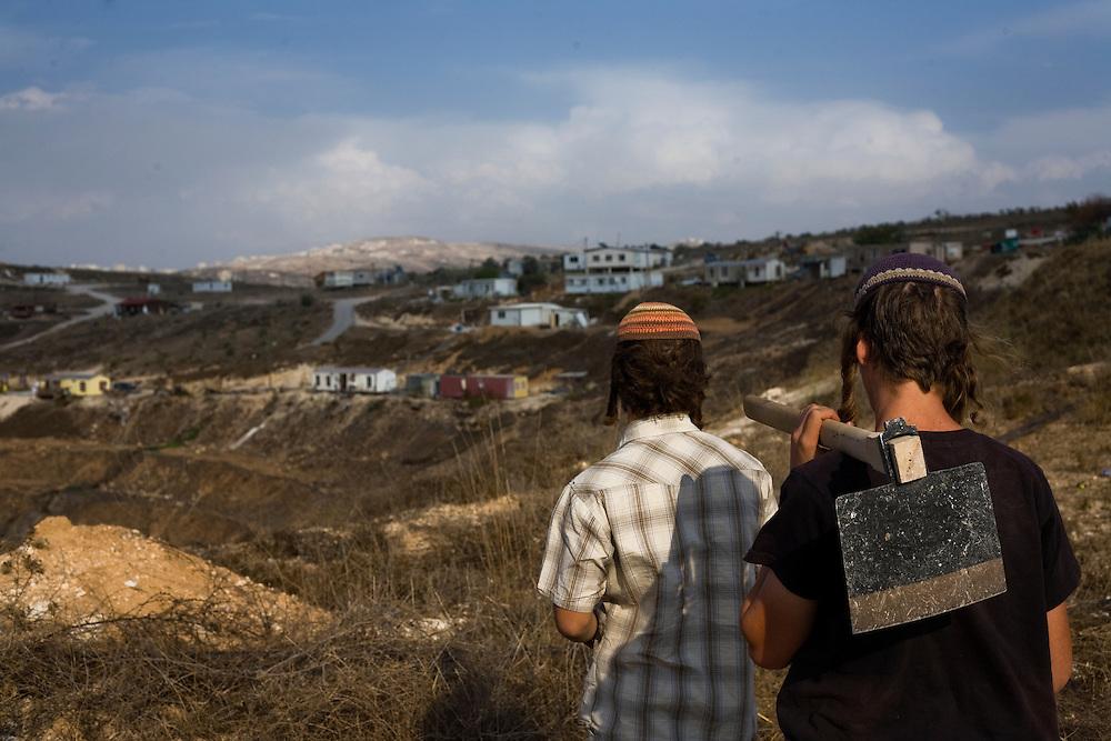 Two Israeli settlers look at the Havat Gilad settlement.