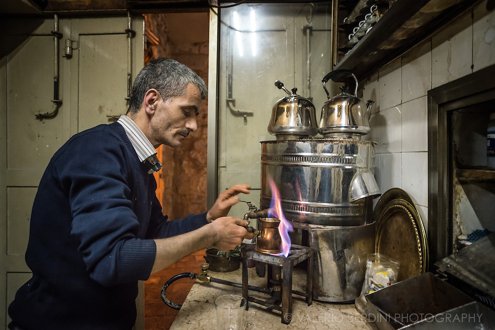 A man prepares an Arabic Coffee in a copper pot. The Arabic coffee brewing method is common throughout Middle-East, coffee is brewed without the addition of sugar and cardamom is often added.