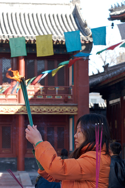 A bundle of incense is lit for a prayer at Yonghegong.  This Tibetan Temple is known to tourists as Lama Temple and it's located in Dongcheng District Beijing, China. This is the largest Temple of its kind outside of Tibet.  In 1723 the structure was turned into a Temple after the resident became the third Qing Emperor.