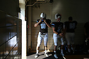 09/20/2014 - Somerville, Mass. - Tufts DL James Brao, E15, fastens his helmet in the locker room before exiting to face Hamilton at Zimman Field on Sept. 20, 2014. (Kelvin Ma/Tufts University)