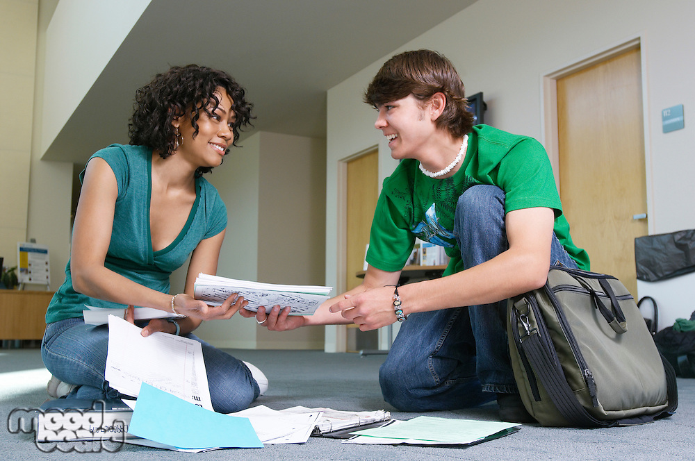 Male student assisting female student, picking up books from floor