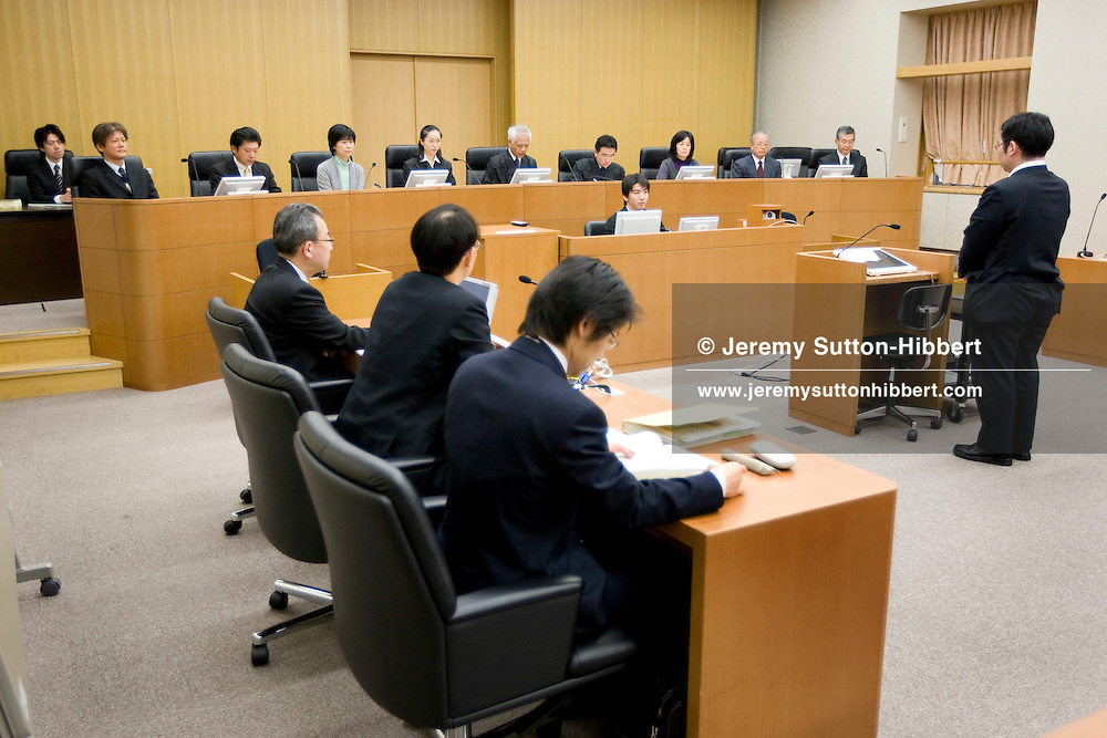 "The three judges and six 'lay judges' ( members of the public forming the jury), in background of photo,  preside over courtroom proceedings during a mock trial where the defendant was accused of ""accidental mortality"" (and found innocent), in Saitama District Court, in Urawa town, Saitama city, Japan, Friday 27th February 2009. The mock trial is part of the process of introducing the 'lay judges jury system' to the Japanese law system. Trials with 'lay judge juries' will begin in May 2009."