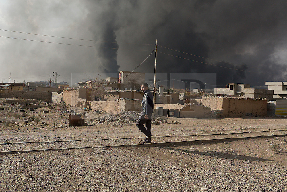 Licensed to London News Pictures. 02/11/2016. Qayyarah, Iraq. A man walks along disused railway tracks as thick smoke rises from boring oil wells, set alight by retreating Islamic State militants, in the town of Qayyarah, Iraq.<br /> <br /> Two months after being liberated from the Islamic State, the Iraqi town of Qayyarah, located around 30km south of Mosul, is still dealing with the environmental repercussions of their ISIS occupation. The town's estimated 15,000 inhabitants constantly live under, and in, heavy clouds of smoke which often envelope the settlement. The clouds emanate from burning oil wells in a nearby oil field that were set alight by retreating ISIS extremists after a two year occupation. The proximity of the fires, often right next to homes within the town, covers many buildings and residents with thick soot and will lead to long term health and environmental implications. Photo credit: Matt Cetti-Roberts/LNP