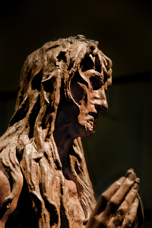 Closeup of Donatello's late sculpture in wood of the penitent Magdalen.  Her mournful face, tangled hair, ragged robe, and wrinkled hands are shown.