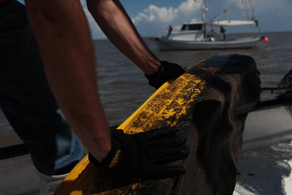 Allen Labat pulling in hard boom around Pelican Island from Delacroix Island, LA August 30, 2010.