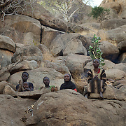 April 28, 2012 - Buram, Nuba Mountains, South Kordofan, Sudan: A group of women sits among the rocks in the mountains outside Buram village in South Kordofan's Nuba Mountains...Since the 6th of June 2011, the Sudan's Army Forces (SAF) initiated, under direct orders from President Bashir, an attack campaign against civil areas throughout the South Kordofan's province. Hundreds have been killed and many more injured...Local residents, of Nuba origin, have since lived in fear and the majority moved from their homes to caves in the nearby mountains. Others chose to find refuge in South Sudan, driven by the lack of food cause by the agriculture production halt due to the constant bombardments of rural areas. (Paulo Nunes dos Santos/Polaris)
