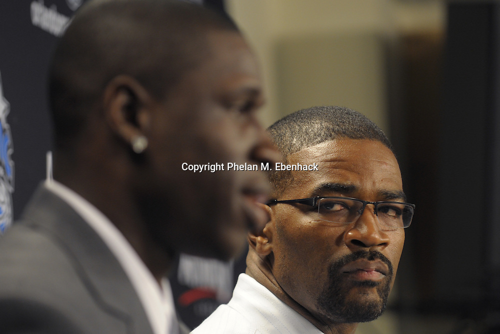Orlando Magic basketball team general manager Otis Smith, right, listens Mickael Pietrus, of France, answers questions after signing his free agent contract with the NBA team during a press conference at the RDV Sportsplex in Maitland, Florida.