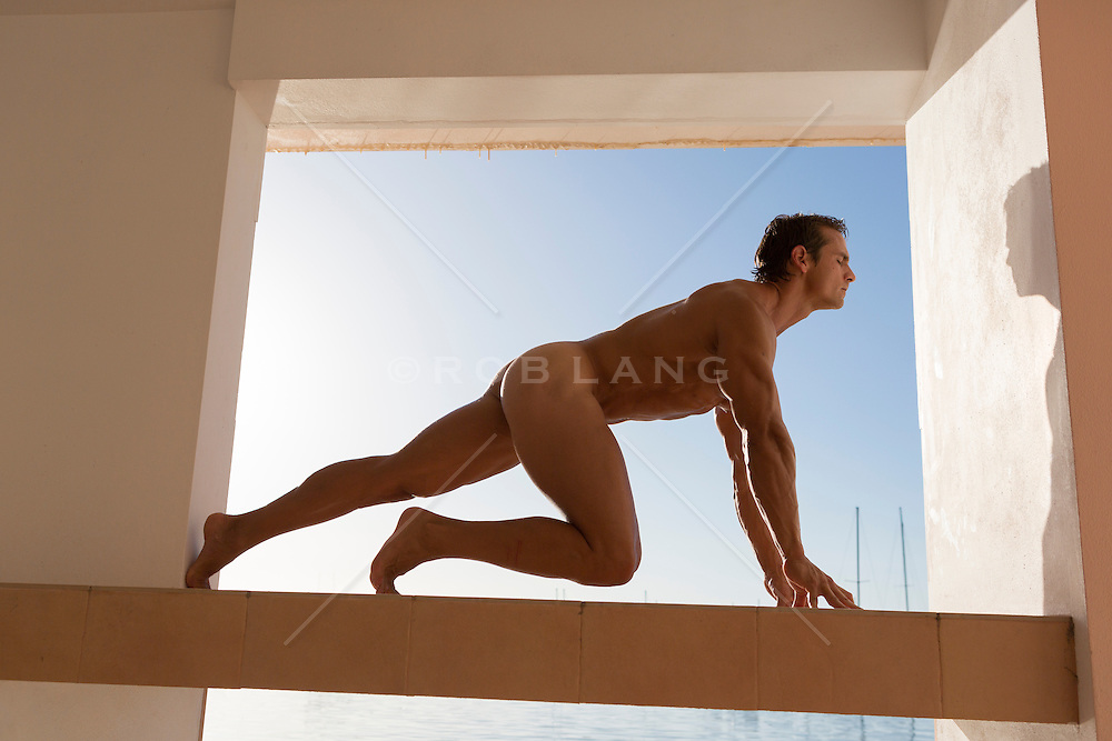 naked man in a window frame outdoors