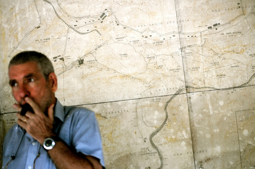 Cacao grower, Kai Rosenberg smokes a cigar infront of a large map of his Monterosa plantation on March 26, 2009 in Choroni, Venezuela.