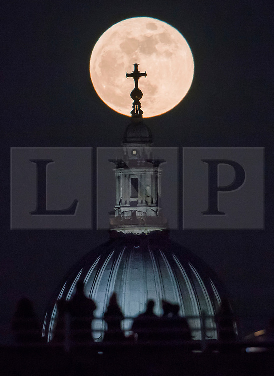 © Licensed to London News Pictures. 31/01/2018. London, UK. Members of the public cross Waterloo bridge in the foreground as a full, blue supermoon rises behind St Paul's Cathedral in central London shortly after sunset. Two full moons in the same calendar month is also know as a blue moon. Photo credit: Ben Cawthra/LNP