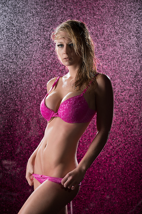 Wet blonde woman wearing pink lingerie posing on a pink background