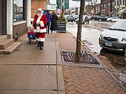 "30 NOVEMBER 2019 - WEST DES MOINES, IOWA: SANTA CLAUS walks up 5th Street, the main business street in West Des Moines, Saturday. He was handing out gifts to children on Small Business Saturday. ""Small Business Saturday"" was first observed in the United States on November 27, 2010, as a counterpart to Black Friday and Cyber Monday, which are generally considered events at malls, ""big box"" stores and e-commerce retailers. Small Business Saturday encourages holiday shoppers to patronize brick and mortar businesses that are small and local. Small Business Saturday is a registered trademark of American Express.       PHOTO BY JACK KURTZ"