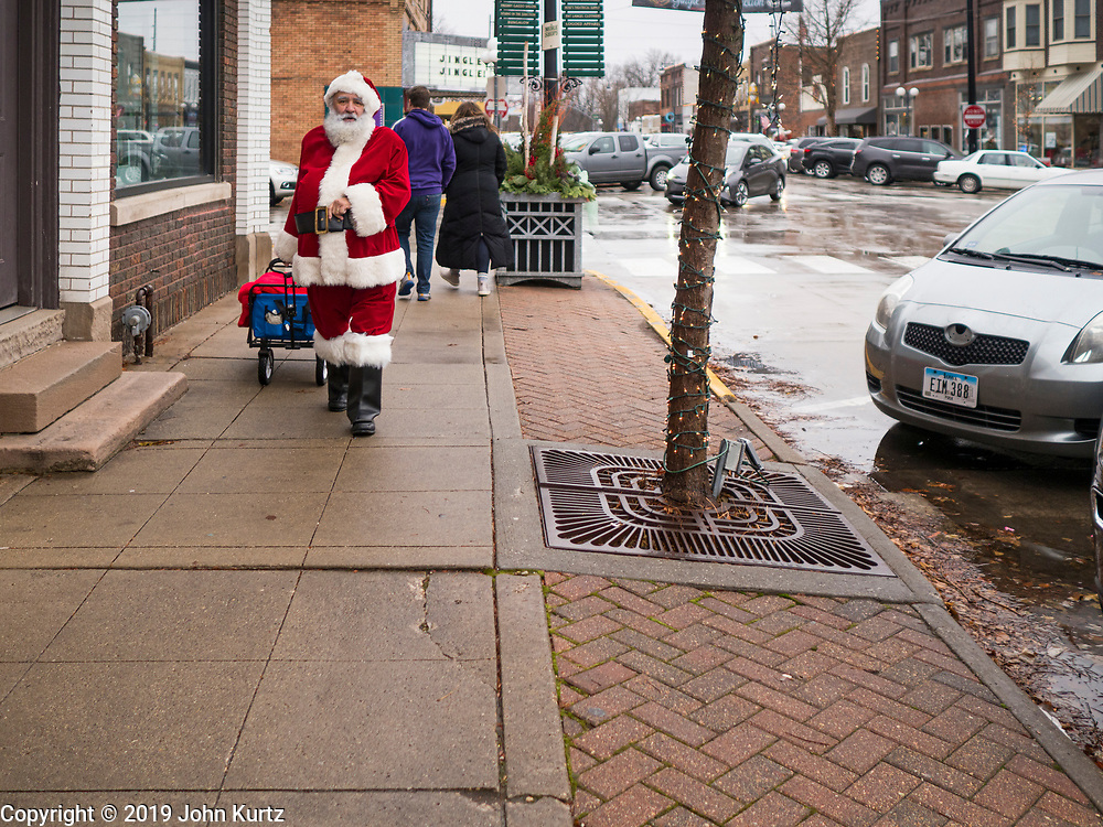 """30 NOVEMBER 2019 - WEST DES MOINES, IOWA: SANTA CLAUS walks up 5th Street, the main business street in West Des Moines, Saturday. He was handing out gifts to children on Small Business Saturday. """"Small Business Saturday"""" was first observed in the United States on November 27, 2010, as a counterpart to Black Friday and Cyber Monday, which are generally considered events at malls, """"big box"""" stores and e-commerce retailers. Small Business Saturday encourages holiday shoppers to patronize brick and mortar businesses that are small and local. Small Business Saturday is a registered trademark of American Express.       PHOTO BY JACK KURTZ"""