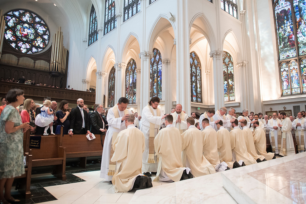 DENVER, CO - MAY 13: Priests take turns laying their hands on the ordinandi during their ordination to the priesthood at the Cathedral Basilica of the Immaculate Conception on May 13, 2017, in Denver, Colorado. (Photo by Daniel Petty/for Denver Catholic)