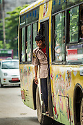 13 JUNE 2013 - YANGON, MYANMAR: A bus ticket collector leans out of his bus in traffic in Yangon. Yangon, formerly Rangoon, is Myanmar's commercial capital and used to be the national capital. The city is on the Irrawaddy River and has a vibrant riverfront.    PHOTO BY JACK KURTZ