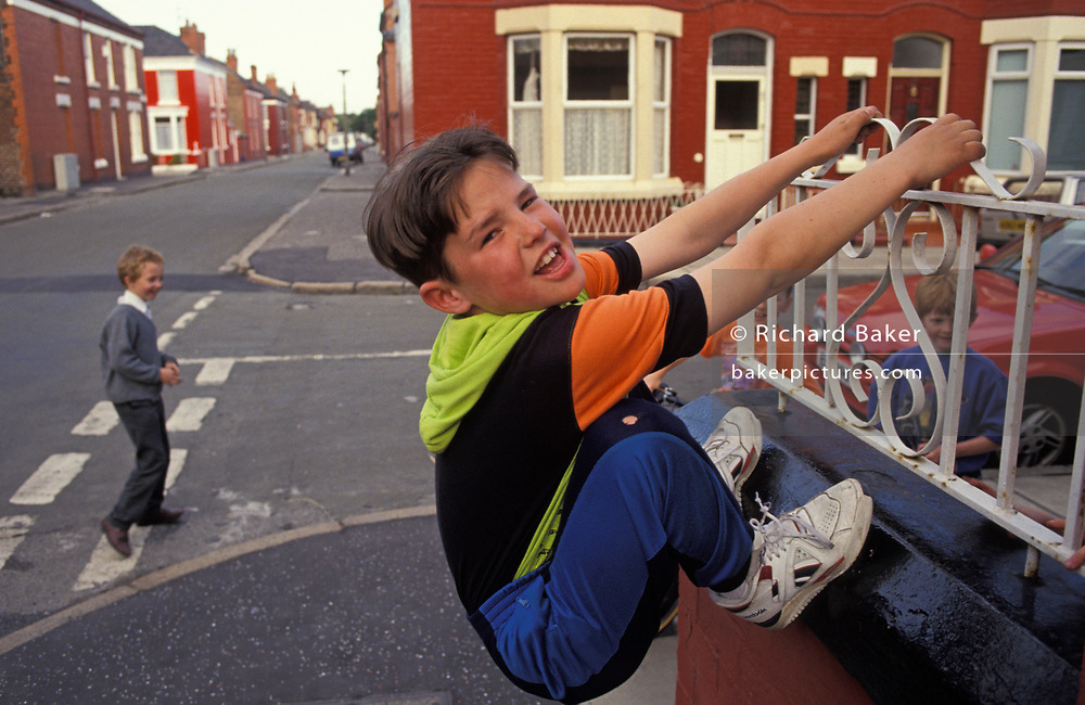 A young boy plays with his mates in a street corner in the Aigburth district of Liverpool, on 14th June 1991. Aigburth is a suburb of Liverpool, England, bordered by Dingle, Toxteth, Sefton Park, Mossley Hill, Garston and Grassendale.