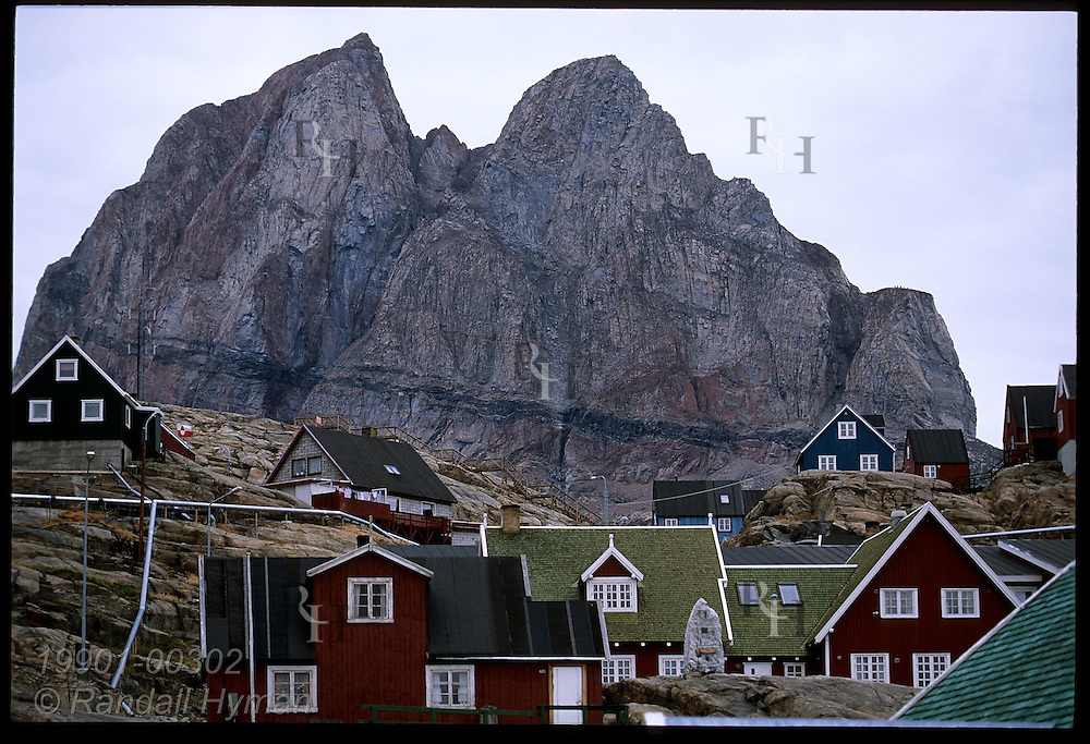 Twin red gneiss peaks (1170m tall) tower over colorful wooden homes clinging to town's rocky slopes; Uummannaq, Greenland